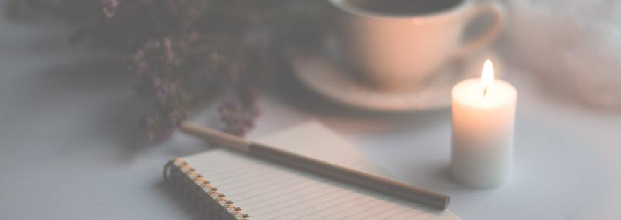 Rule notebook with pencil on top beside small lit white candle and tea cup and saucer